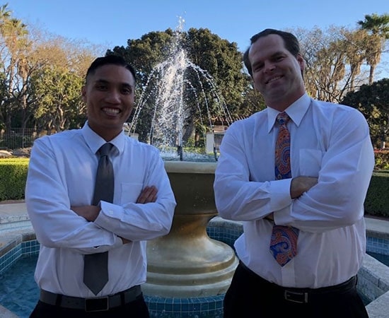 Dr. Acasio & Dr. Carson in front of office fountain.
