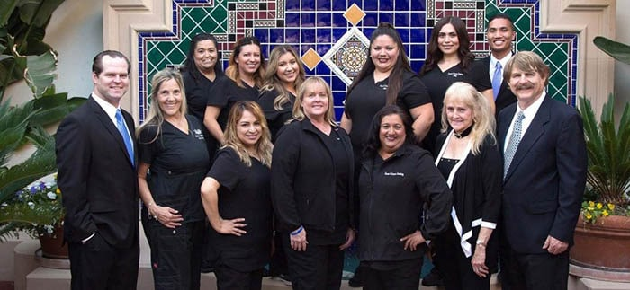 Oxnard dental staff in front of office fountain